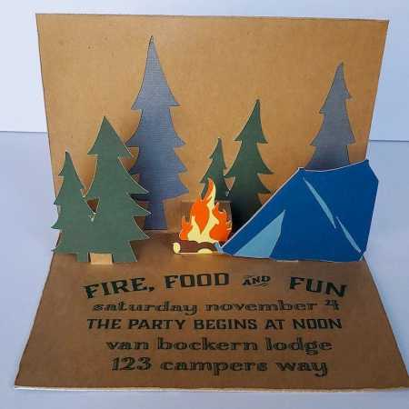 """Invitation opened in front of white background. Invitation is brown craft paper with deep blue tree cutouts, deep green tree pop ups, yellow and orange campfire popup, and blue tent. Text in deep green reads """"FIRE, FOOD AND FUN; saturday november 4; THE PARTY BEGINS AT NOON; van bockern lodge; 123 campers way"""""""