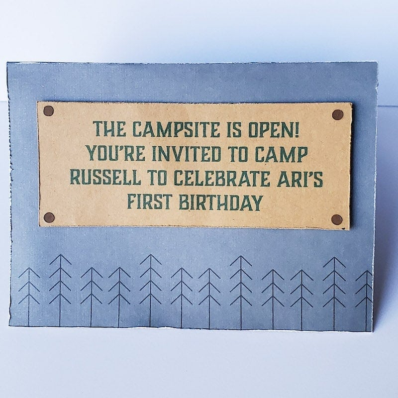 """Front of the invitation, closed. Dark blue/gray with dark brown stick trees along the bottom. Raised brown rectangle with dark green text """"THE CAMPSITE IS OPEN! YOU'RE INVITED TO CAMP RUSSELL TO CELEBRATE ARI'S FIRST BIRTHDAY"""""""