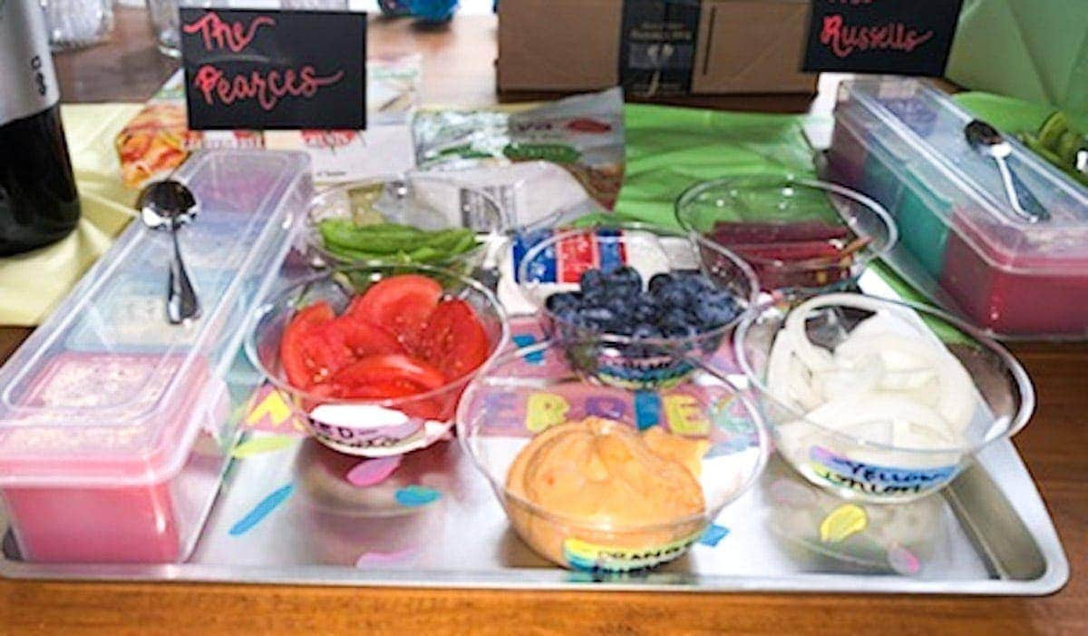 Tray with storage container, individual bowls with tomatoes, green peppers, hummus, blueberries, onions, and purple carrots in them