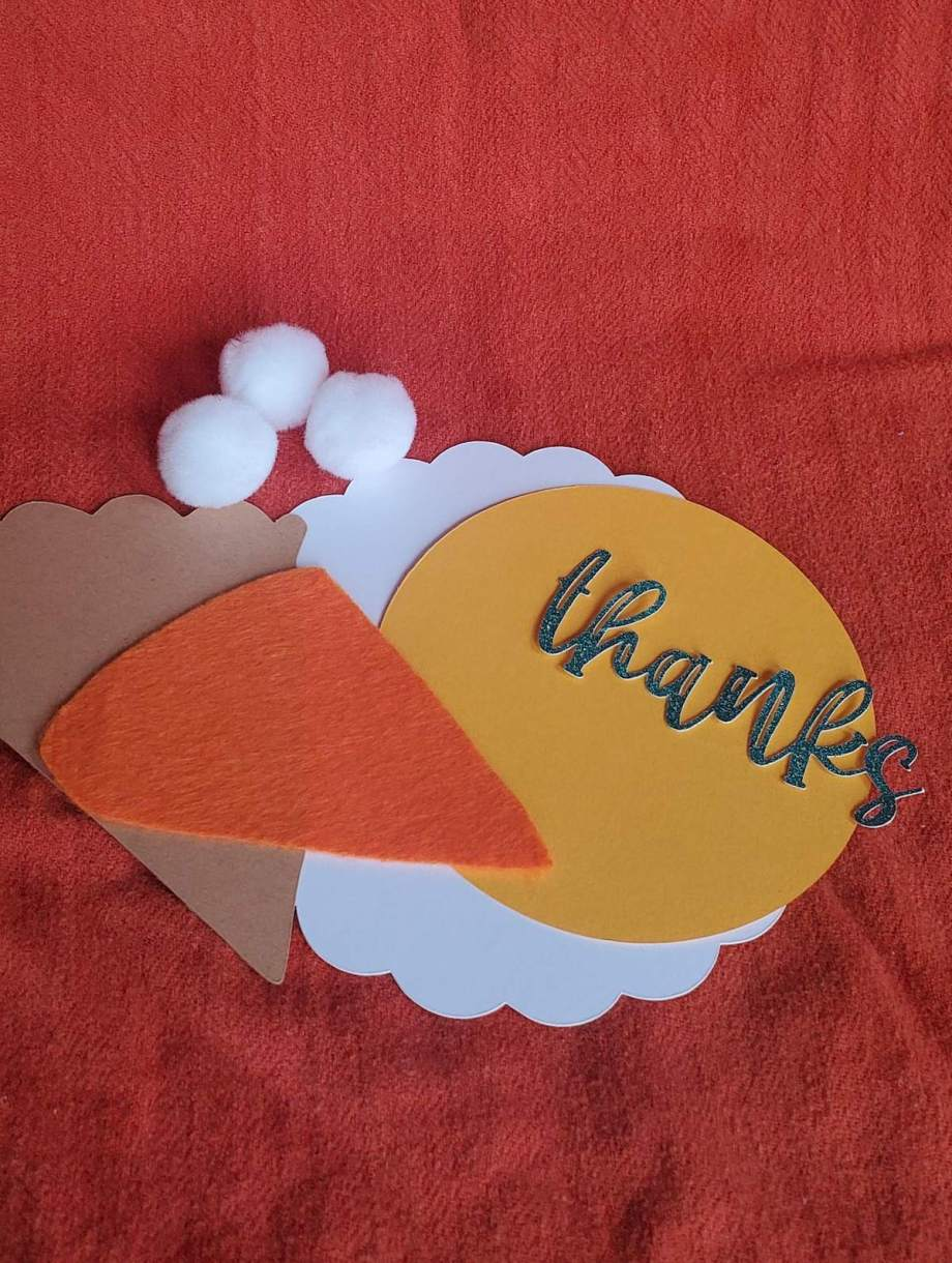 photo of pieces of pumpkin pie made out of cardstock, kraft board, felt, with pom poms, white scallop plate, yellow plate, thanks in glittery green. All on an orange background