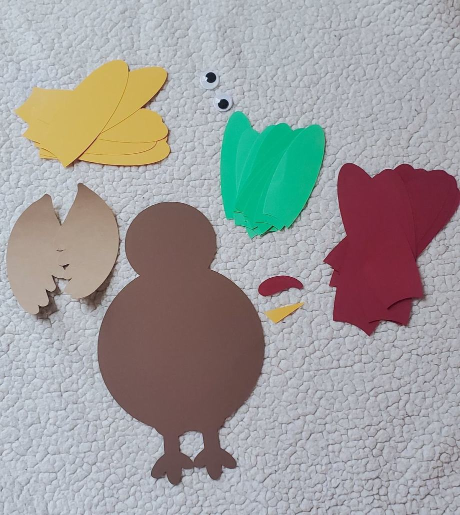 Photo of turkey made from cardstock, with sets of feathers in yellow, green, red, wings out of faux suede
