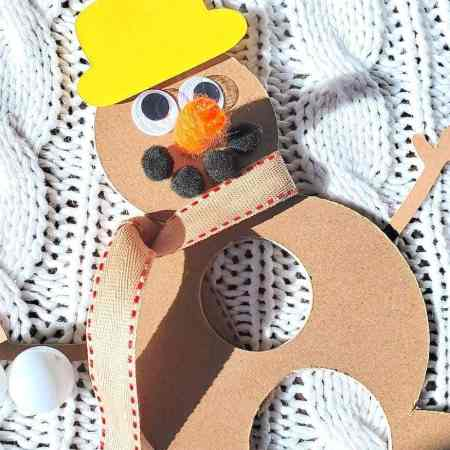 Photo of snowman made from chipboard, pom pom smile, yellow hat, orange carrot nose, googly eyes, mini ping pong ball, ribbon scar