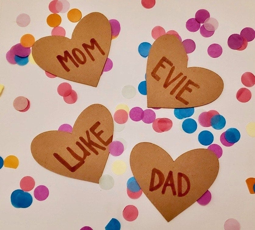 Photo of 4 brown hearts on top of confetti; one heart says Mom, one says Dad, Luke, and Evie