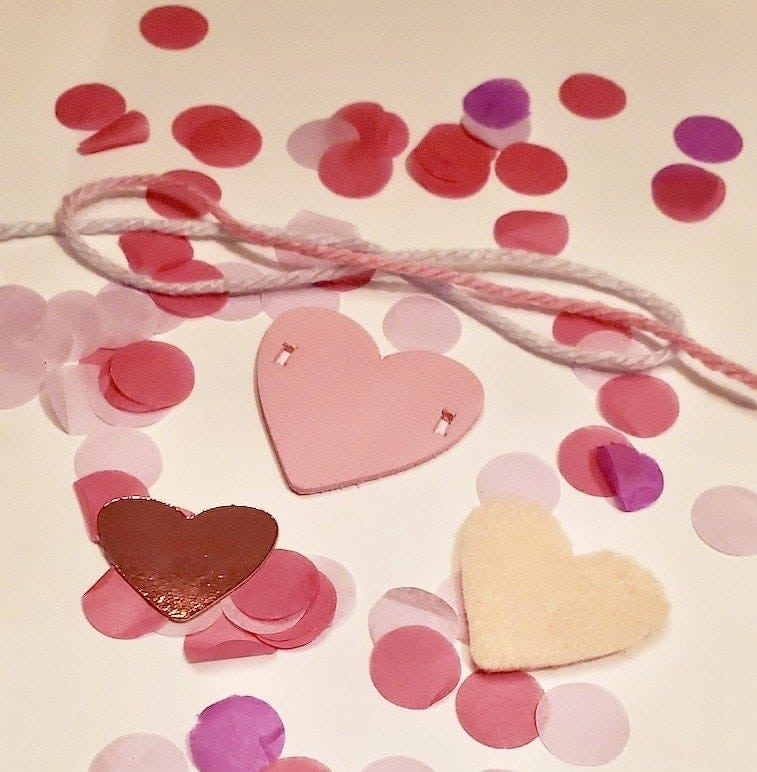 Picture of three pink hearts, pink ribbon, and pink confetti