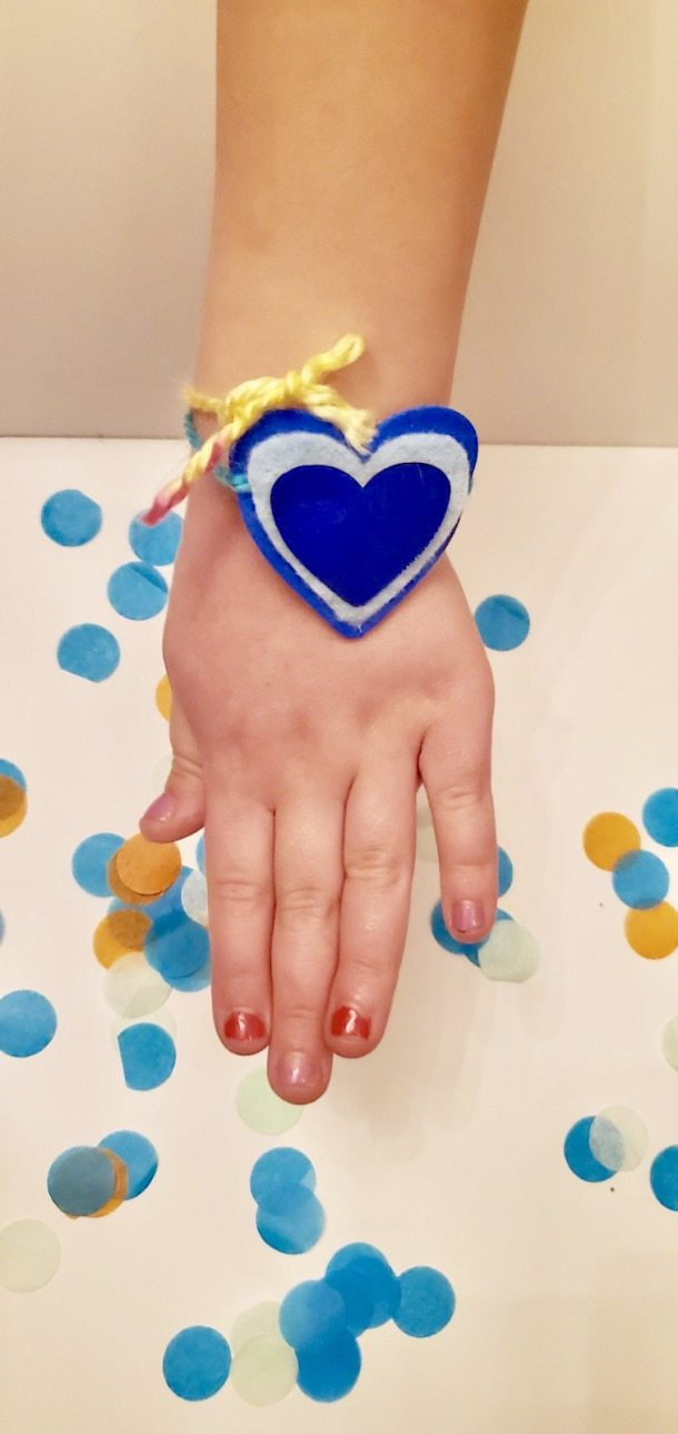Picture of an arm wearing a bracelet with 3 blue hearts