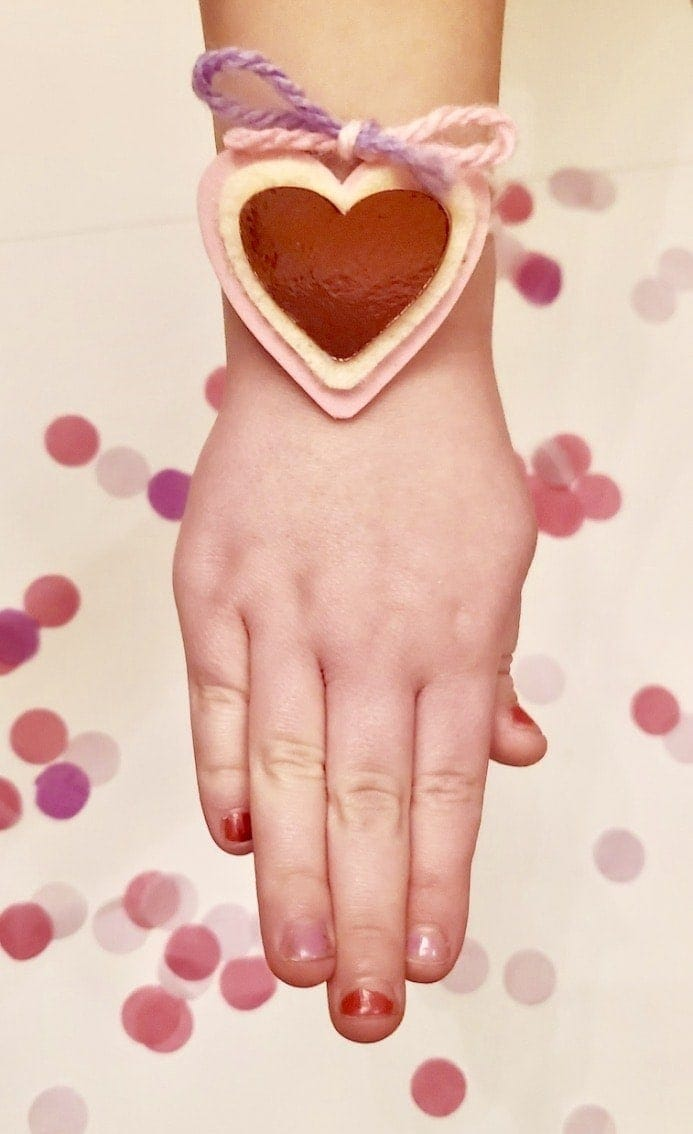 Picture of an arm wearing a bracelet with three pink hearts