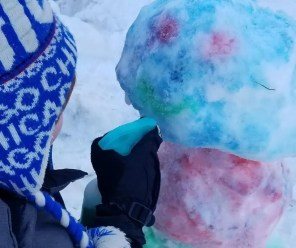 Making a snowman using snow paint a fun outdoor activity for kids.