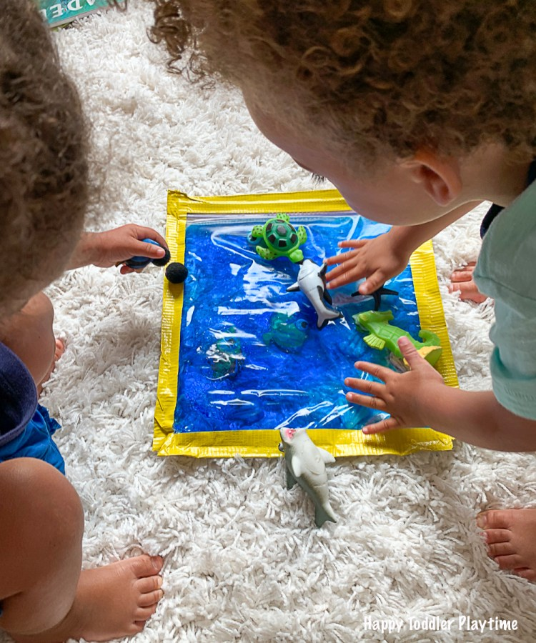Toddlers playing with an ocean sensory bag with ocean animals