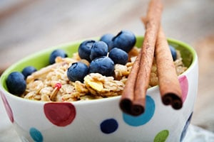 photo: ginger pear blueberry crumble in poka-dot bowl with cinnamon sticks