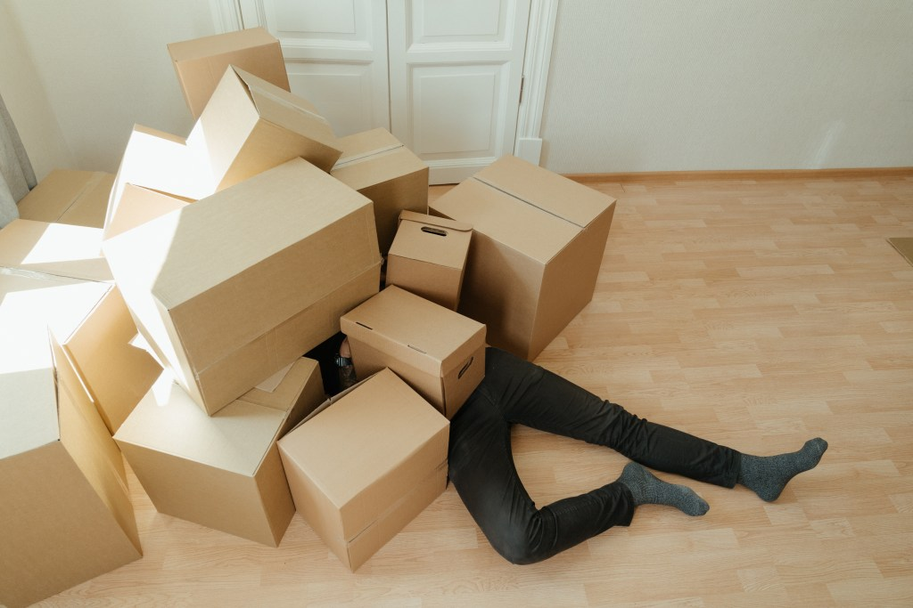 man falling under boxes