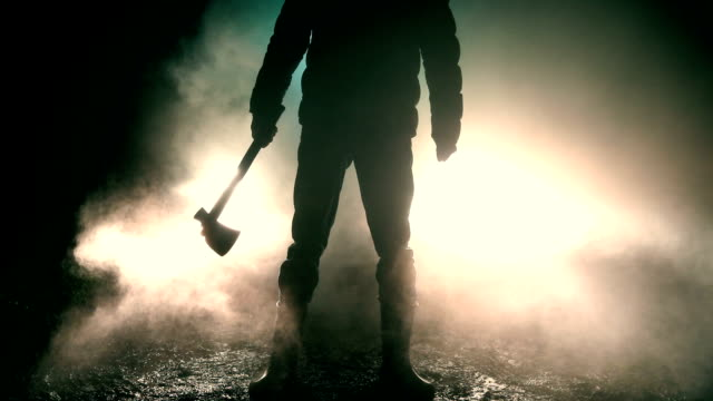 Man holding axe standing in front of car
