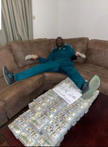 Scott Sakupwanya posing in front of US $5 million cash