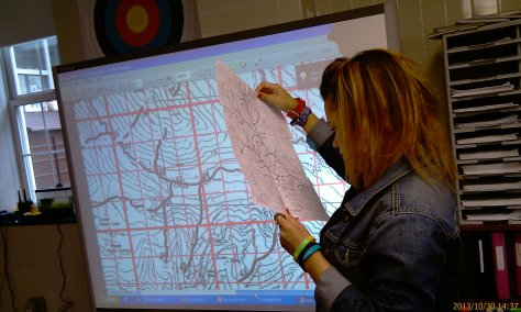 12th grader, Makayla, using a map she assembled to find pollution sources dumping in a river.