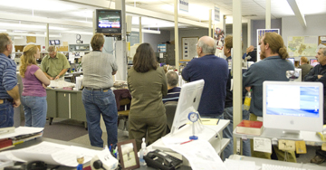 Members of The Chieftain news staff gather around television sets as the presidential race is called for Barack Obama.