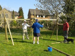 Three men putting together wooden frames