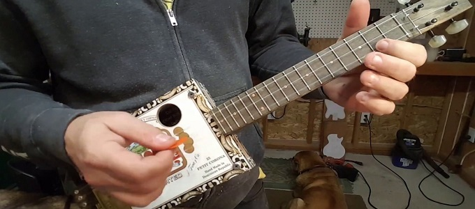 Ilustrasi: Pria Memainkan Ukulele 3 String (credit: Youtube/Puckett Cigar Box Guitar)