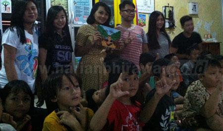 Keenam mahasiswa UK Petra Jurusan DKV foto bersama puluhan anak-anak eks Lokalisasi Dolly di Taman Bacaan Masyarakat (TBM) RW 11 Putat Jaya, Kamis (1/12) kemarin. [gegeh bagus setiadi]