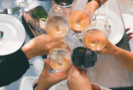 five wine glasses with different wines