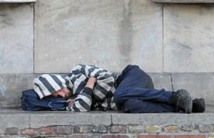 A homeless man sleeping on a wall