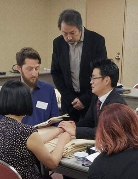 Japanese Acupuncture study-abroad tourにて参加者の脈を診る足立繁久と通訳される前田篤希先生