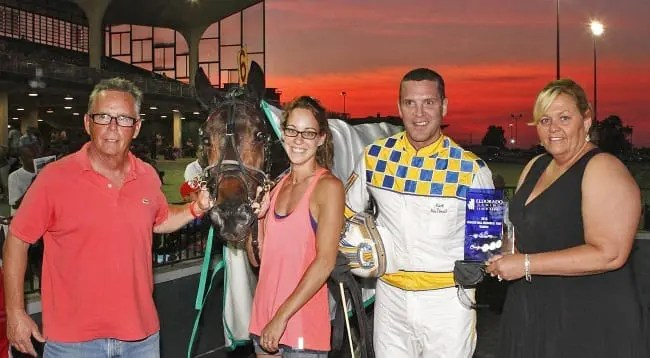 Obrigado's trainer and part-owner Paul Kelley (left) is joined in the Scioto Downs winner's circle by caretaker Jenna Caligaris and driver Mark MacDonald after winning Saturday's $210,000 Charlie Hill Memorial | Brad Conrad
