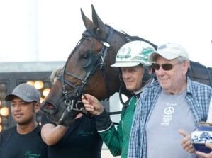 Dave Landry Six Pack, Ake Svanstedt and part-owner Jeff Gural beside the 1:49.1 world record teletimer after winning the 126th edition of the Kentucky Futurity.