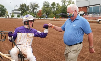 Mark Hall / USTA | David Miller congratulates Joe Holloway after Perfect Sting wins at Red Mile in 2020.