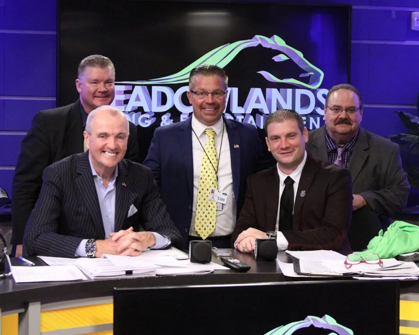 Michael Lisa | New Jersey Governor Phil Murphy (bottom left) was an enthusiastic supporter of Meadowlands Pace Night and posed with the broadcast and management team of (from left) Dave Brower, Jason Settlemoir, Gabe Prewitt and Dave Little.