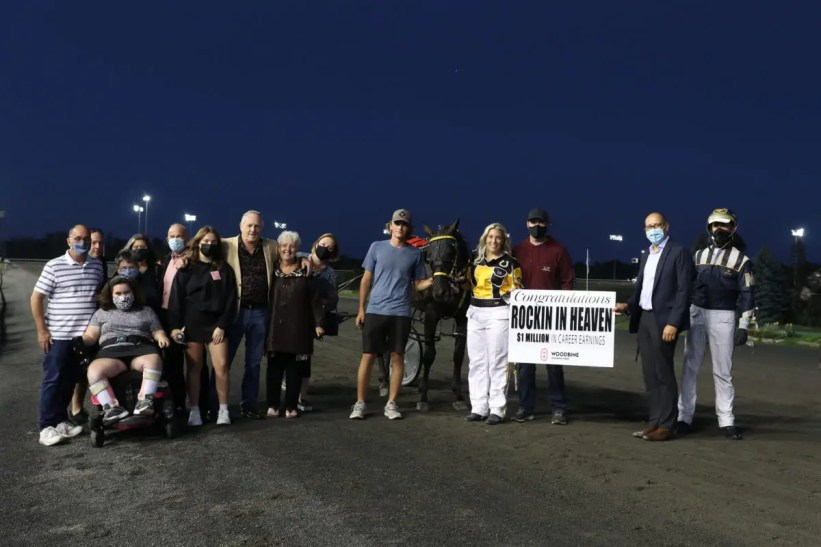 New Image Media   Trainer Teesha Symes (directly left of the sign) on the night Rockin In Heaven went over $1 million at Woodbine Mohawk Park.