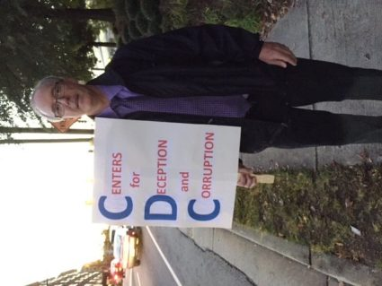Scott Lasiter protesting in front of what he terms the Centers for Deception and Corruptions. Photo Credits: (c) 2015 Harold Michael Harvey