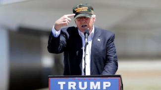 "Republican presidential candidate Donald Trump gestures to a his camouflaged ""Make America Great"" hat as he discuses his support by the National Rifle Association at a campaign rally at the Redding Municipal Airport Friday, June 3, 2016, in Redding, Calif. (AP Photo/Rich Pedroncelli)"
