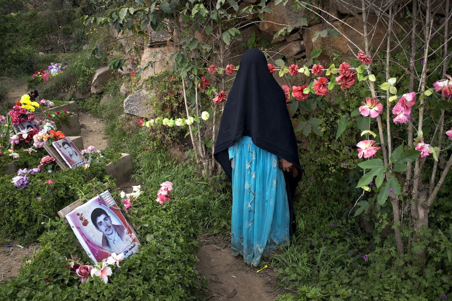 A young girl visits the martyrs cemetery, which is dedicated to the men who died protecting Hussein Al Houthi.