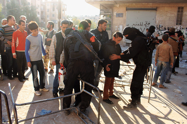 Fighters with Jabhat al-Nusra search residents at a checkpoint in Aleppo, Syria, October 2013 © Molhem Barakat/Reuters
