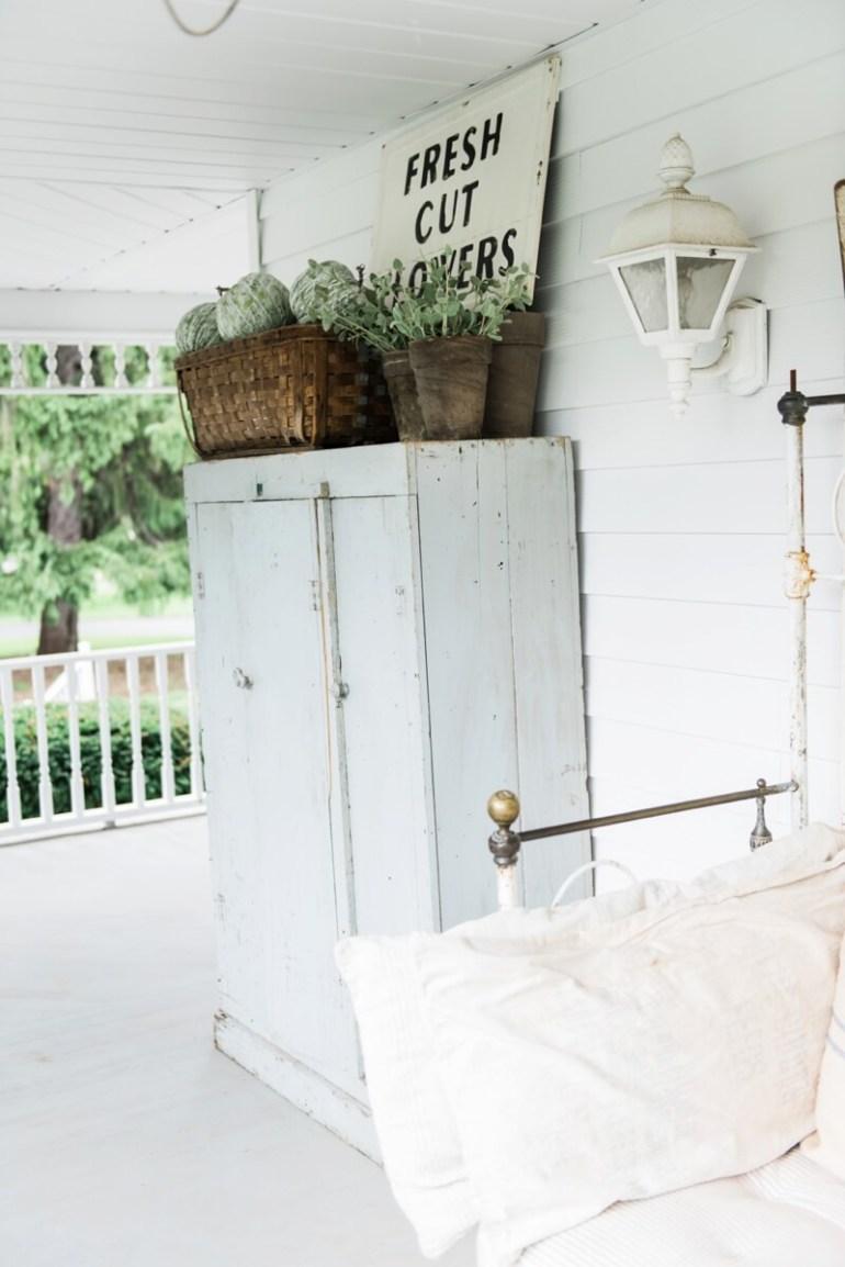 Farmhouse Porch Decorating Ideas - Whitewashed Wooden Porch Cabinet & Sign - Harpmagazine.com