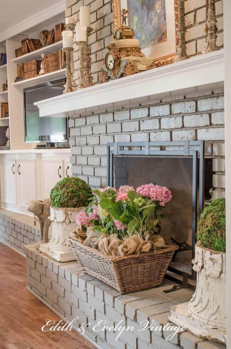 French Country Decor Ideas - Grey Brick Fireplace with Potted Spring Flowers - Harpmagazine.com