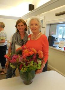 Suzanne Bushnell was the first lucky winner in the raffle pictured here with Sara and her arrangement.