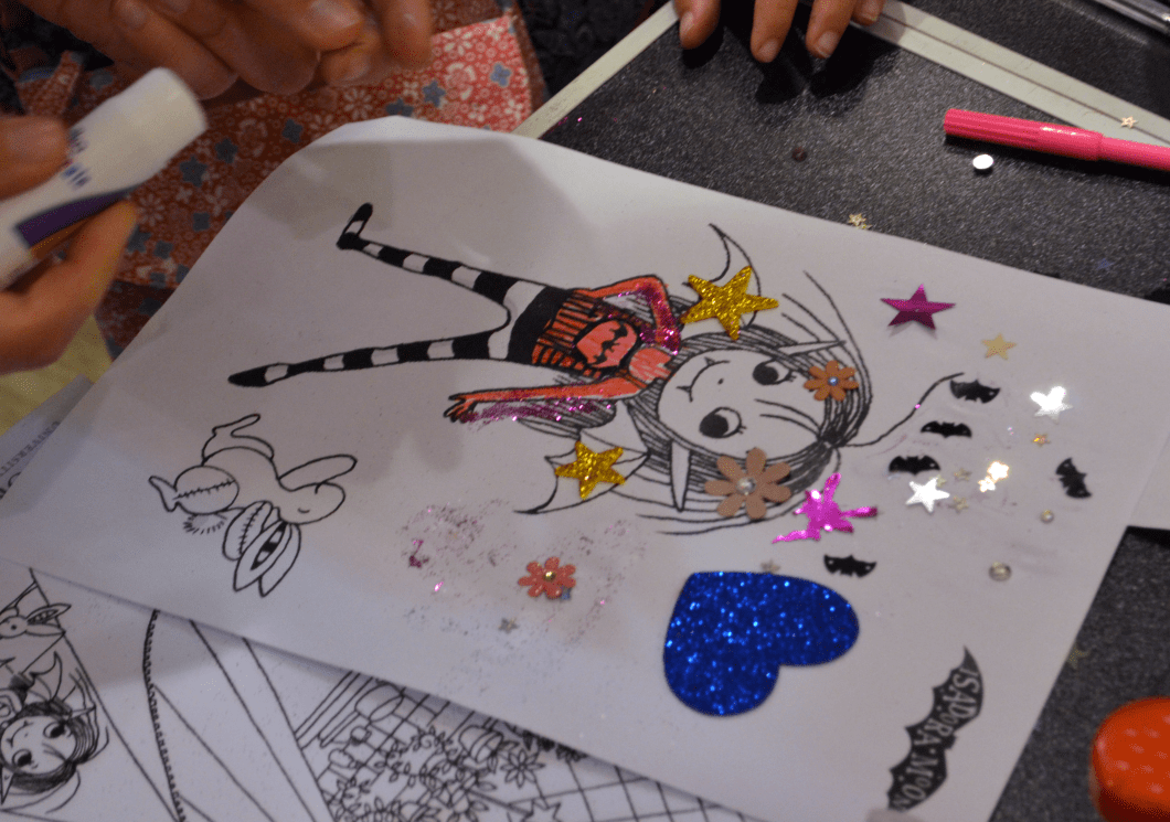 Sticking on glitter shapes at Harriet Muncaster's Isadora Moon event at St Albans Waterstones