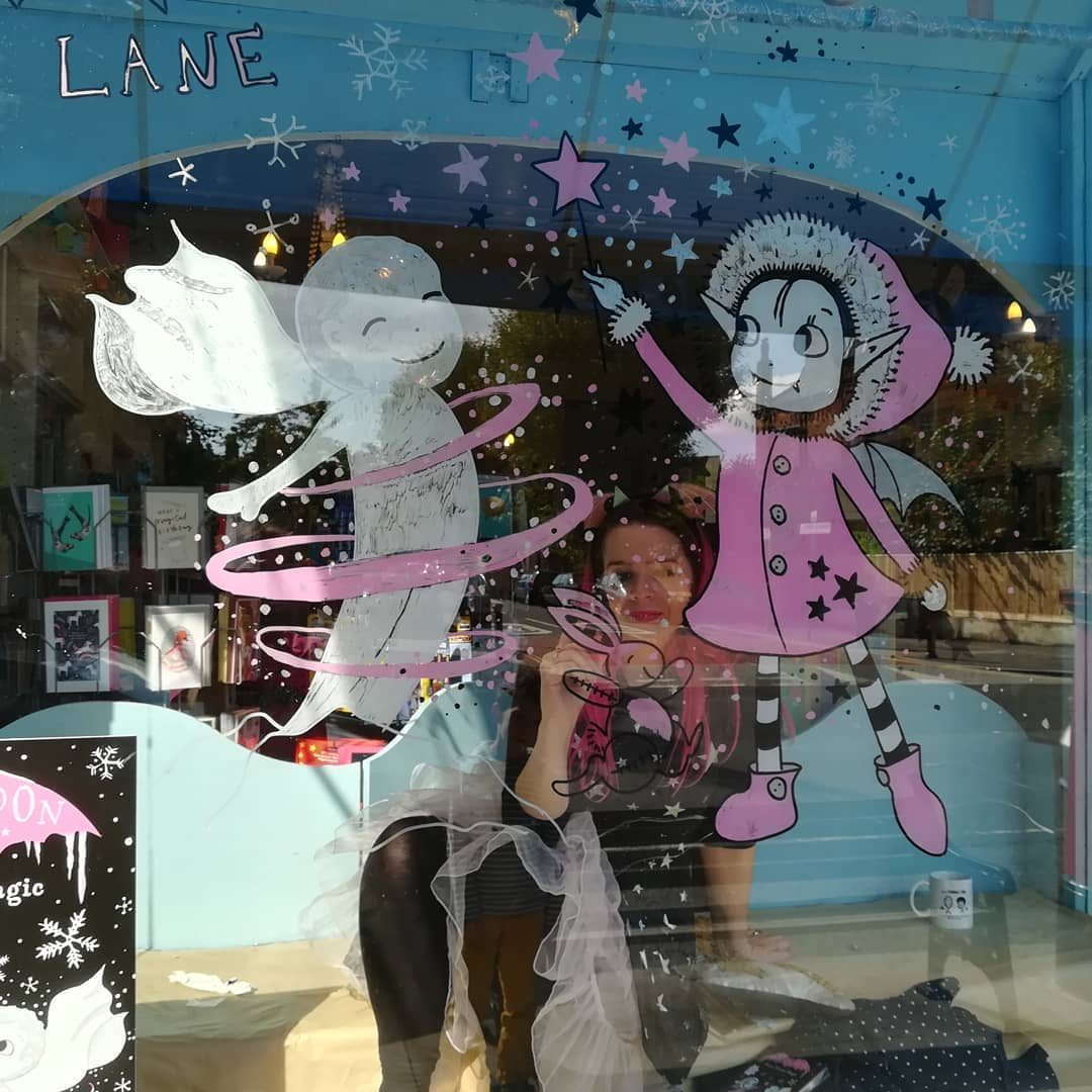 Harriet Muncaster painting window display for Tales on Moon Lane