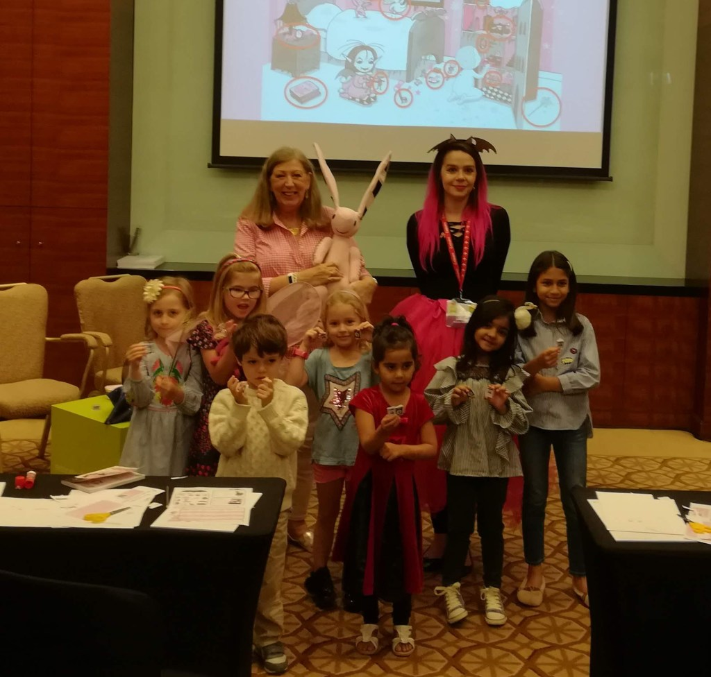 Harriet Muncaster with children showing off Isadora Moon mini books at a workshop event