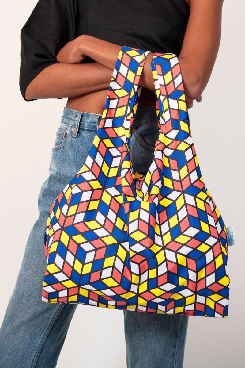 person holding kind bag geometric design