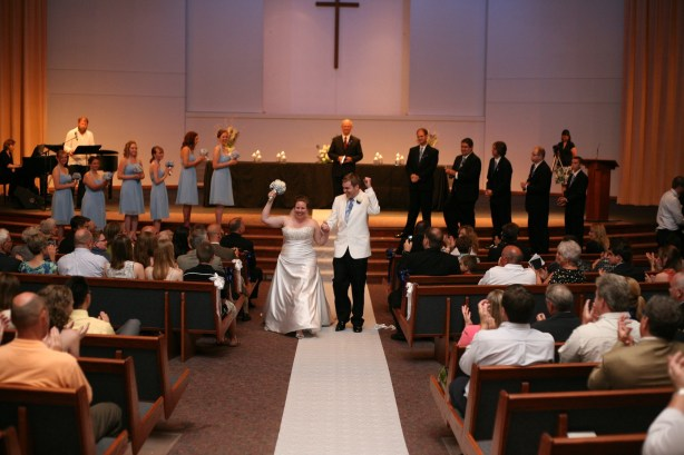bride-and-groom-walking-down-aisle-with hands-in-air-in-victory