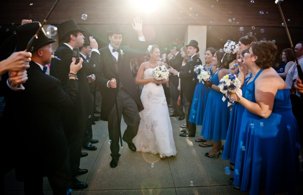 bride-and-groom-leaving-wedding-ceremony-surrounded-by-guests
