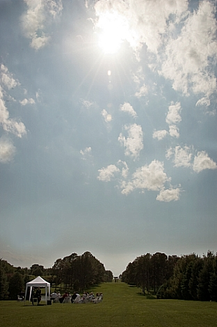 Bright sun in clouds above an outdoor wedding in a grassy park