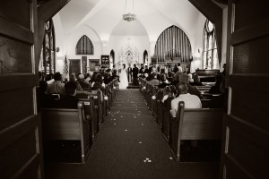 Looking down the aisle at a church to a bride and groom standing at the altar