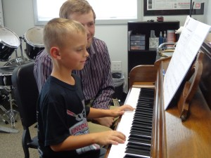 Student playing piano with his teacher looking on
