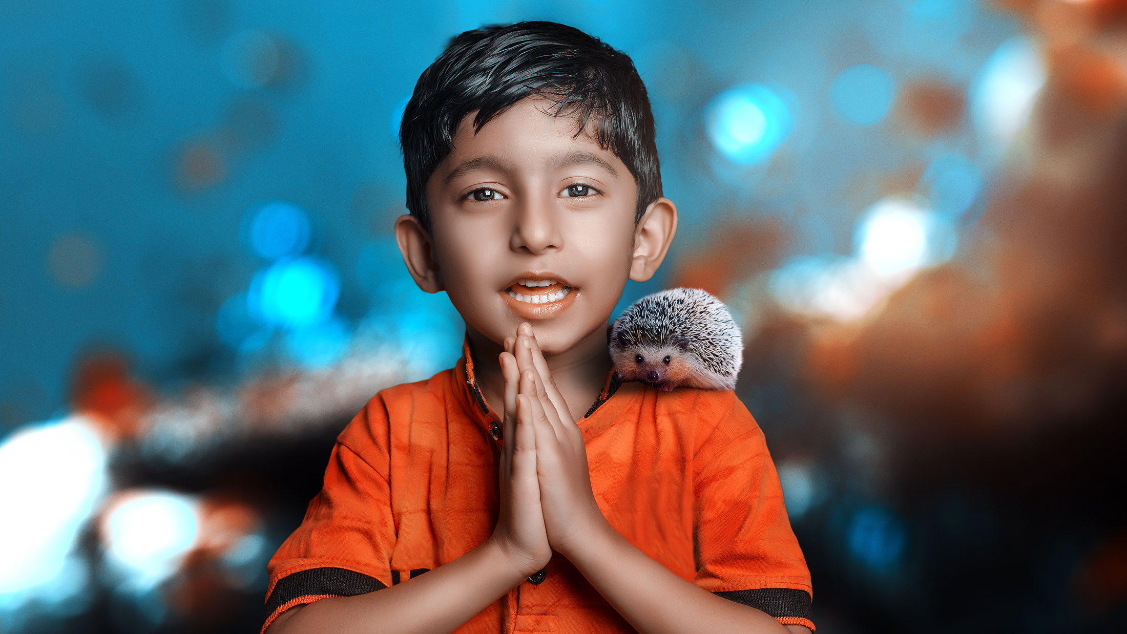 Adorable cute Indian asian caucasian boy child saying namaste welcoming with hedgehog on shoulder on bright vivid bokeh background at night front view looking at camera