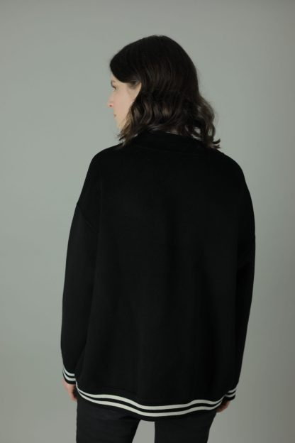 The Anna 100% cashmere double-face Bomber is the ultimate luxury of varsity style. Oversized, and beautifully crafted with its striped and ribbed trims, this bomber is designed with comfort, style and durability in mind. Back view.