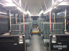 """Interior of #1104X. Notice the plush, high-back, reclining seats and luggage racks? Also, even though this is a Gillig Low Floor transit bus, only the front section with the sideways-facing ADA seats are on the """"low floor"""" end of the chassis. The rest of the seating are situated on higher platforms."""