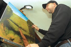 Joe Loganbill of rural Newton works on a painting in December in his home studio. The Newton artist started painting seriously at the age of 40. Photo by Wendy Nugent
