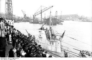 Bild: U-67 beim Einlaufen in Frankreich im Hafen von Lorient am 18. August 1942. Die Überlebenschance der U-Boot Fahrer war ohnehin gering, aber mit der Perfektionierung des ASDIC im Jahre 1943 und verbesserten Abwehrwaffen ging sie nahezu gegen Null. Jede Fahrt war ein Himmelfahrtskommando. Bild: Under the licence of Commons:Bundesarchiv. Bundesarchiv, Bild 101II-MW-4429-09 / Dietrich / CC-BY-SA.